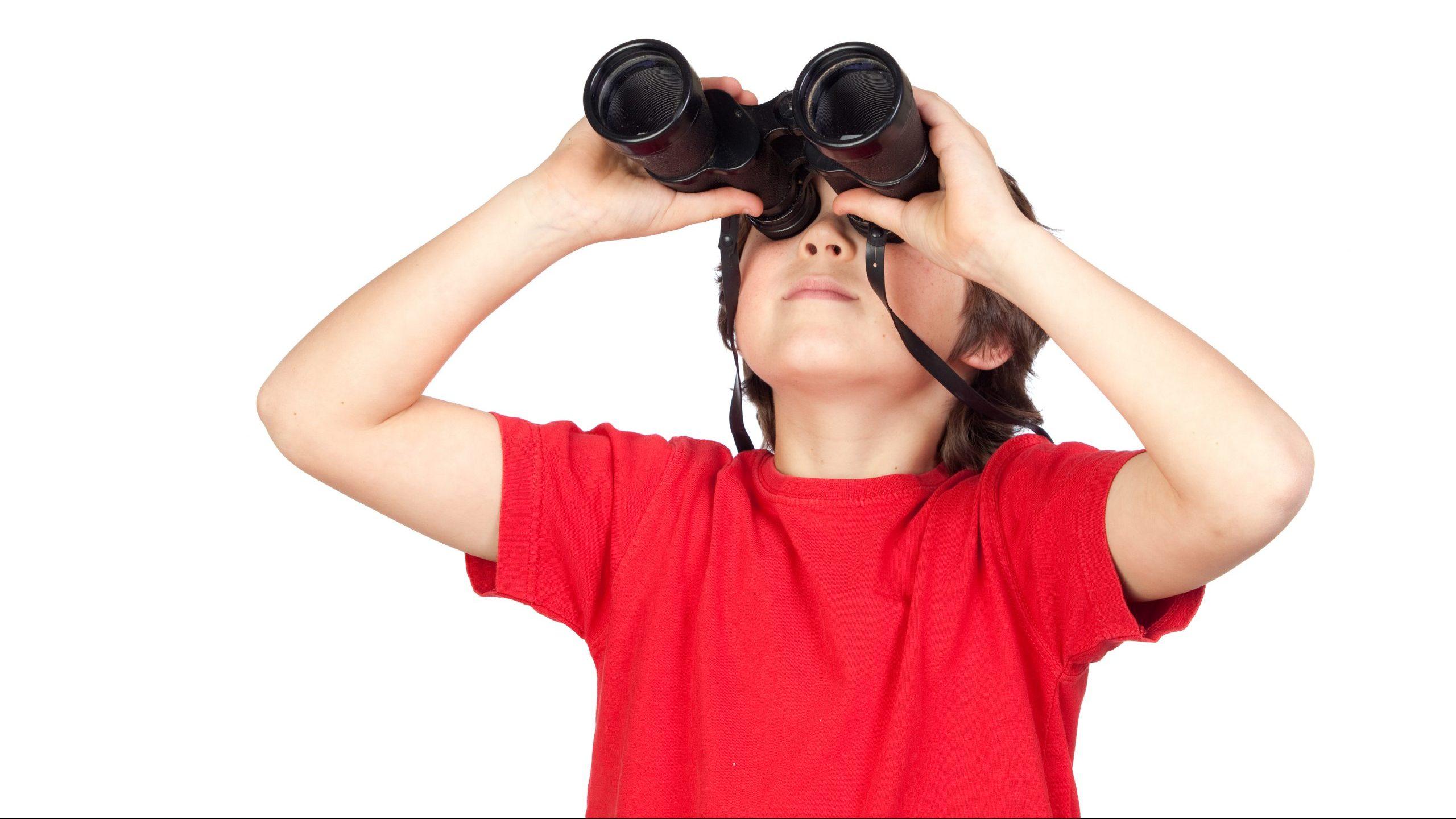 A boy in a red shirt looking through binoculars