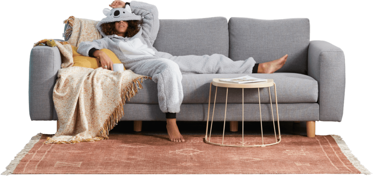 A woman in a koala onesie slouching on a couch