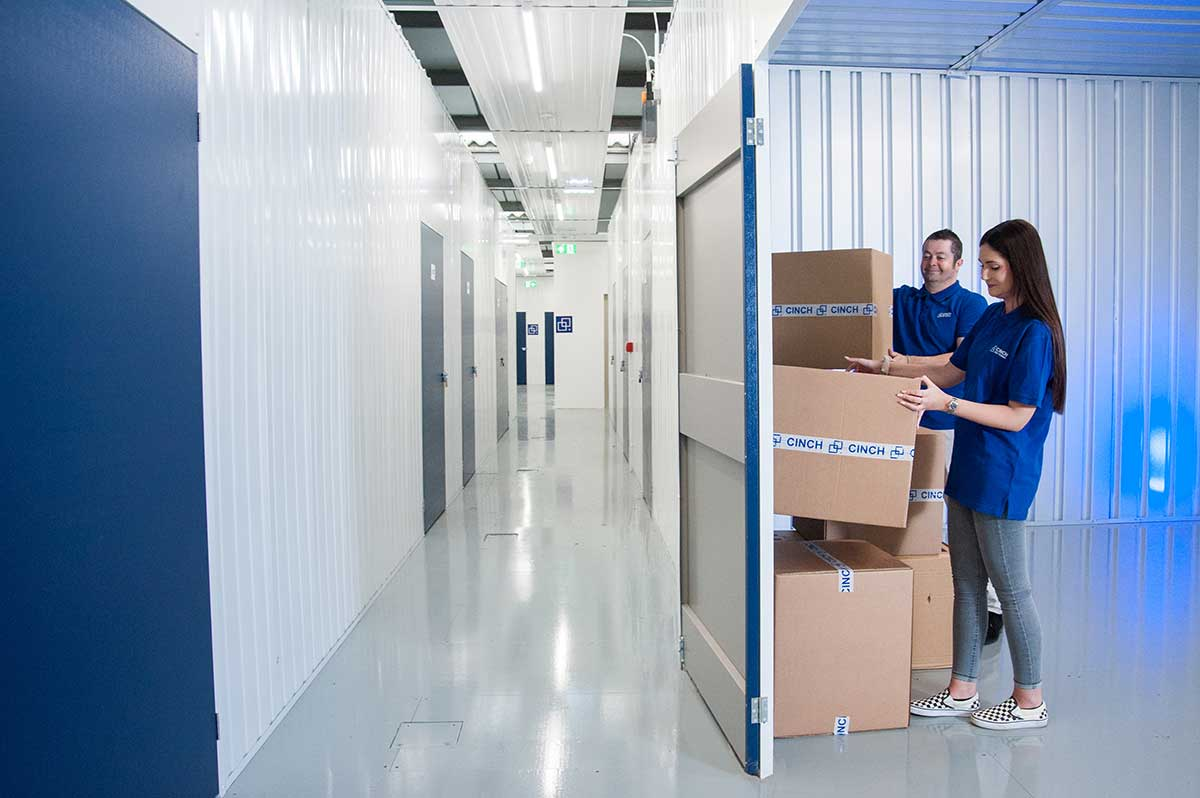 Two employees stacking cardboard boxes in a storage unit