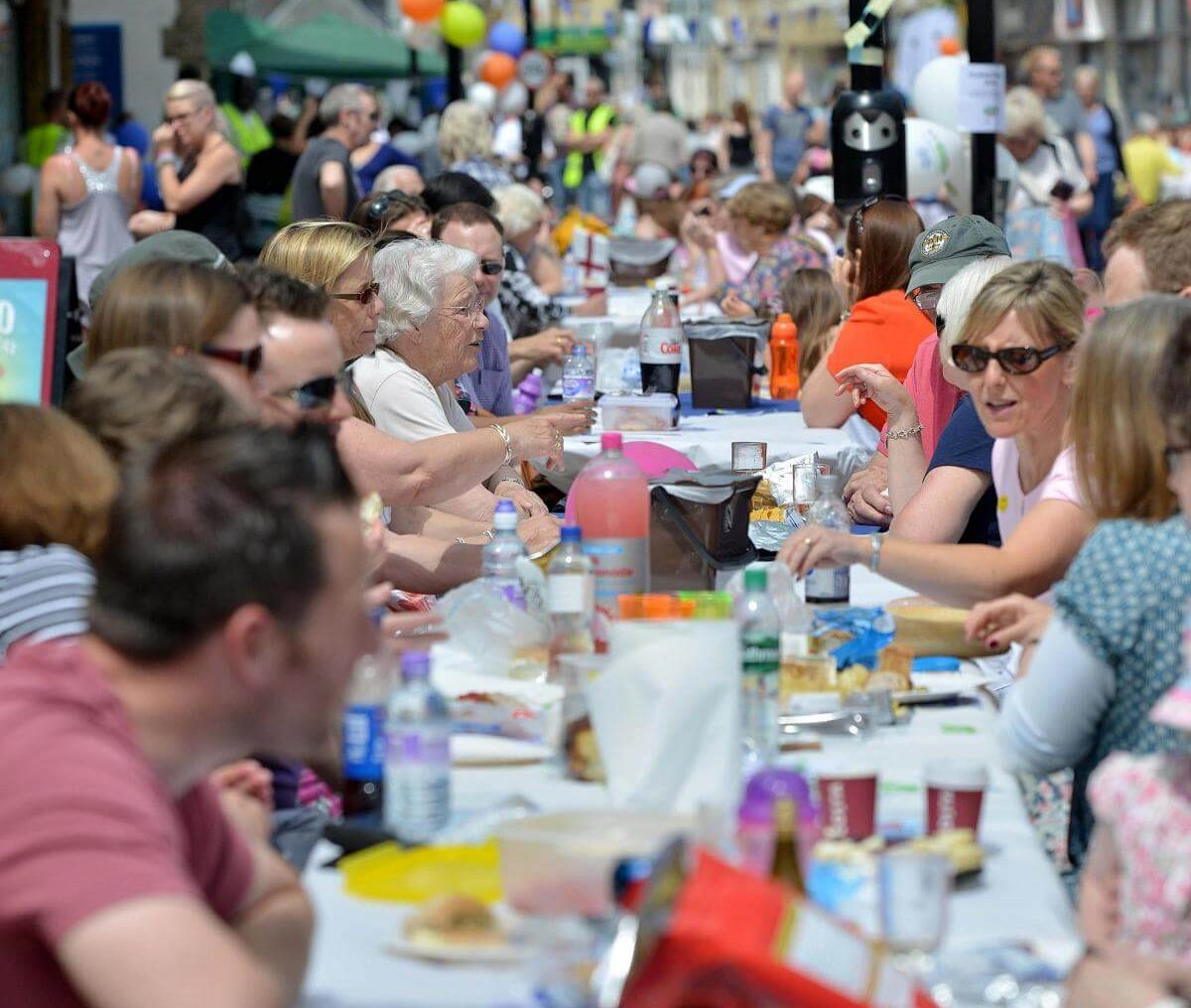 People sharing a long table at a festival