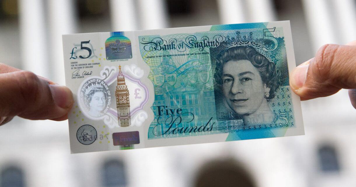 A hand holding a £5 note