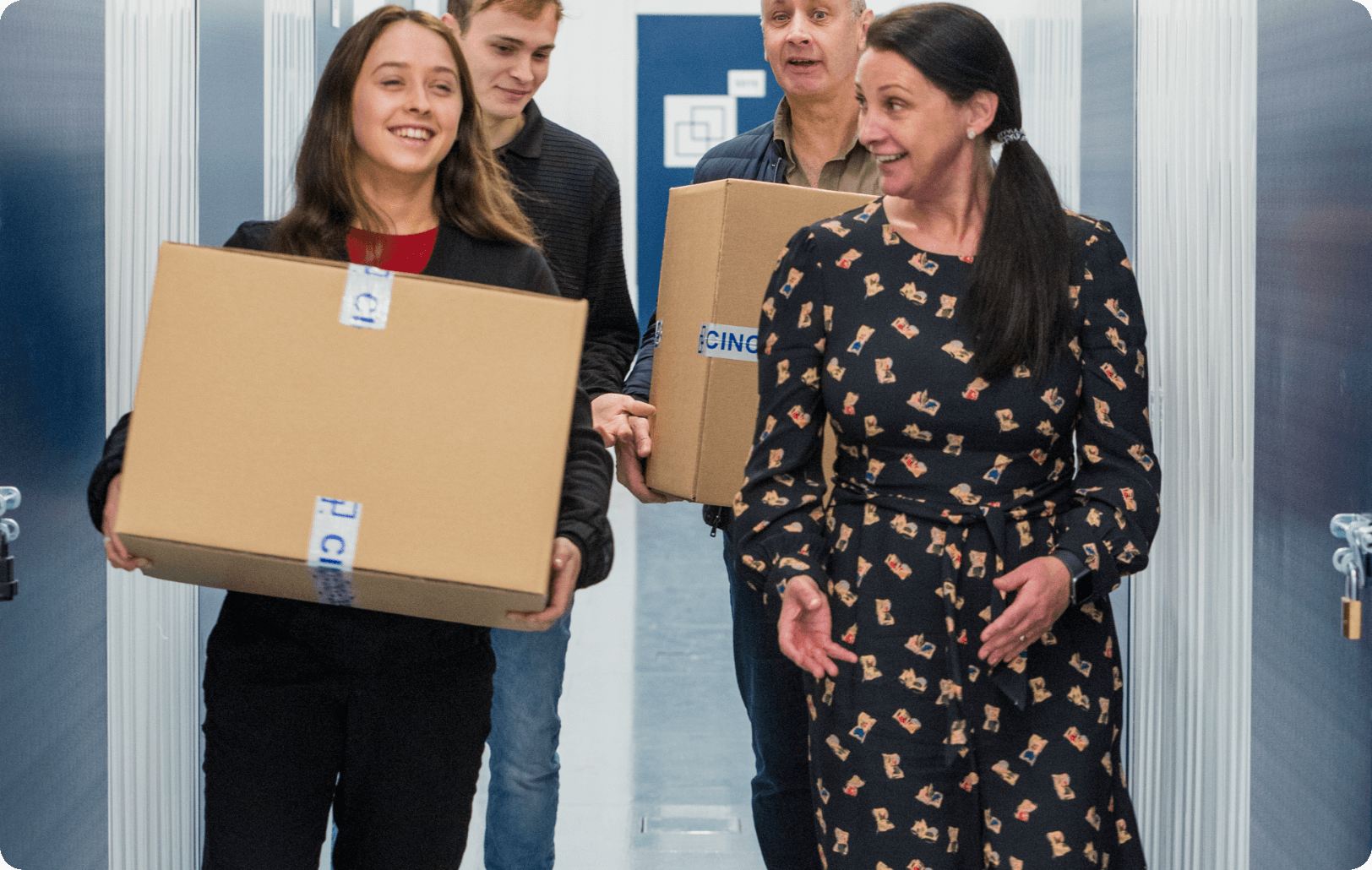 Two people carrying boxes while talking with their friends through a hallway
