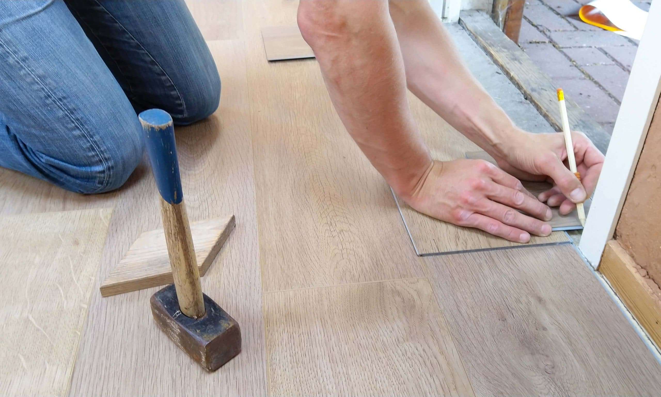A handyman marking the wooden tiles with a pencil