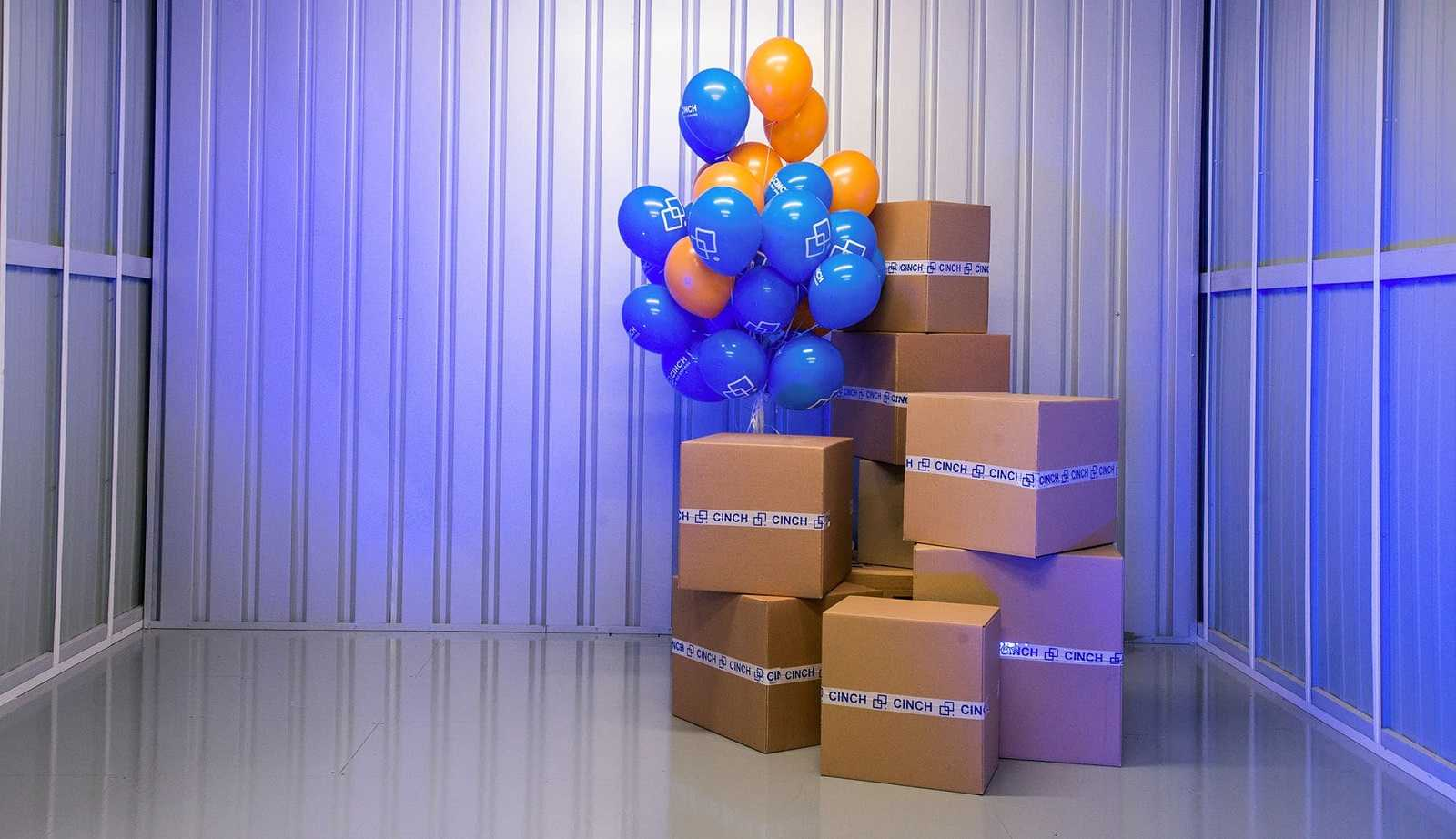 A bunch of balloons tied next to a stack of cardboard boxes inside a storage unit