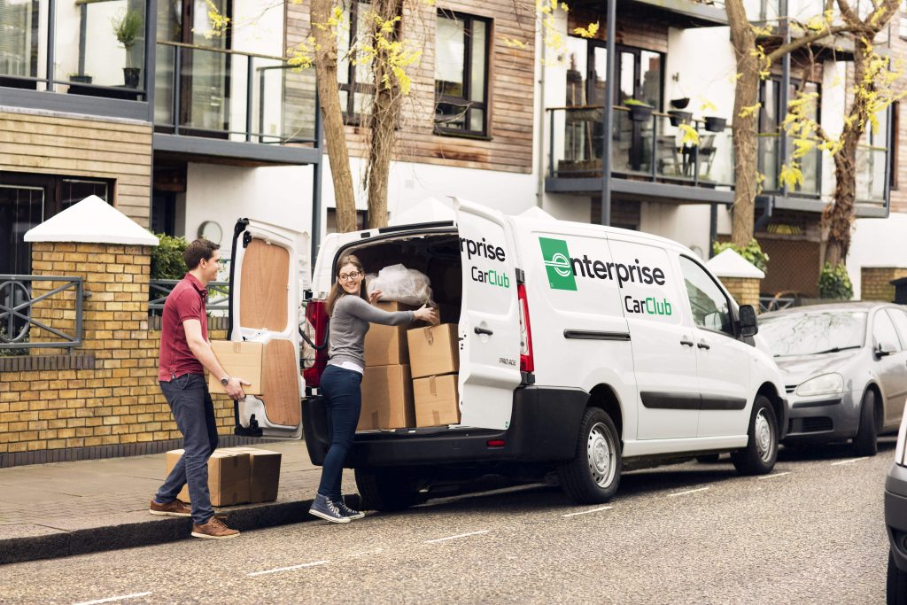 A couple loading cardboard boxes in a moving van