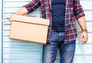 A man holding a box outside storage facility