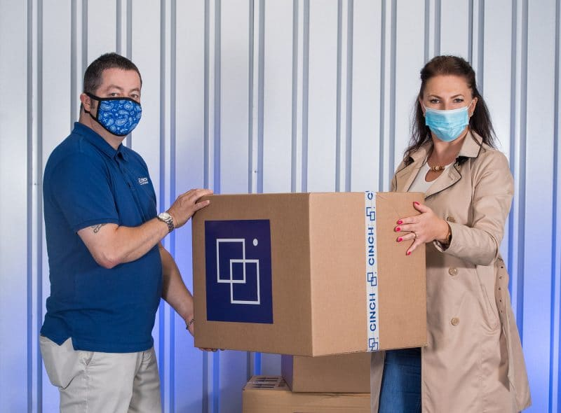 A man and a woman wearing a face mask holding a cardboard box inside a storage unit