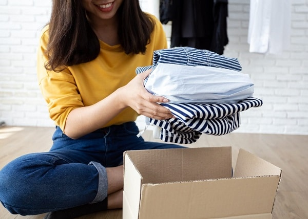 A woman putting folded clothes in a storage box