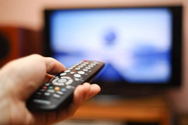 A person pointing a remote control at the TV